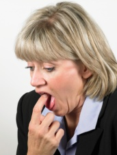 Mature woman with finger in mouth, gagging